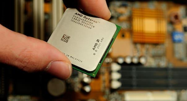 Hand putting cpu processor Advanced Micro Devices AMD Opteron chip in motherboard