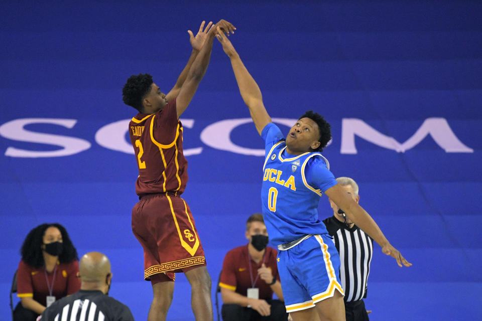Southern California guard Tahj Eaddy, left, shoots and makes a game-winning three-point shot as UCLA guard Jaylen Clark defends during the second half of an NCAA college basketball game Saturday, March 6, 2021, in Los Angeles. USC won 64-63. (AP Photo/Mark J. Terrill)