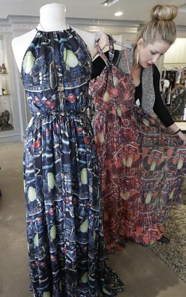 This March 6, 2014 photo shows senior stylist Tiffany Kimbrough adjusting a spring print dress on display at an Elements boutique in Dallas. (AP Photo/LM Otero)