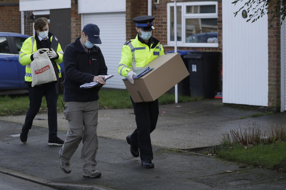 A police volunteer carries a box of home testing kits for COVID-19 from Britain's Department of Health as they go house-to-house distributing them to residents, in Woking, England, Tuesday, Feb. 2, 2021, during England's third national lockdown since the coronavirus outbreak began. British health authorities plan to test tens of thousands of people in a handful of areas of England, including parts of Woking, in an attempt to stop a new variant of the coronavirus first identified in South Africa spreading in the community. The Department of Health says a small number of people in England who had not travelled abroad have tested positive for the strain. (AP Photo/Matt Dunham)