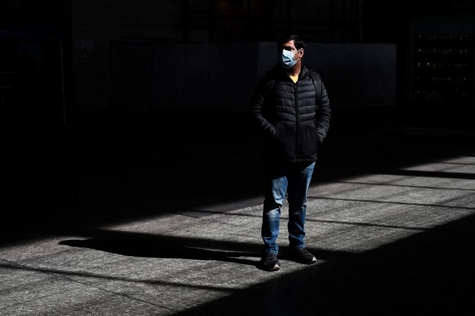 A man in a mask stands outside alone in Italy.