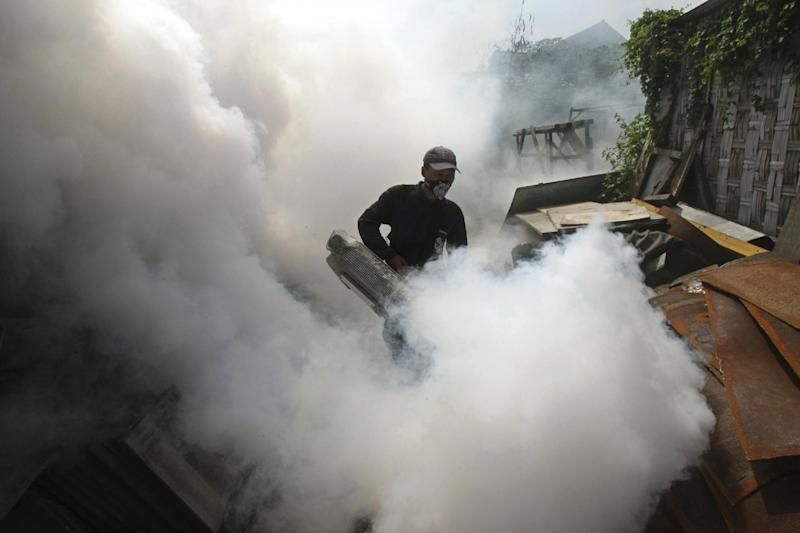 FILE- A health ministry worker discharges anti-mosquito spray as a preventive measure to control dengue fever, in Sidoarjo, East Java, Indonesia, in this file photo dated Thursday, March 14, 2013. According to new research published online Sunday April 7, 2013, in the journal Nature, the number of infected cases is around 390 million, nearly four times as many people infected with the tropical disease than was previously believed, although many develop a mild form of the illness and don't need medical attention. (AP Photo/Trisnadi, File)