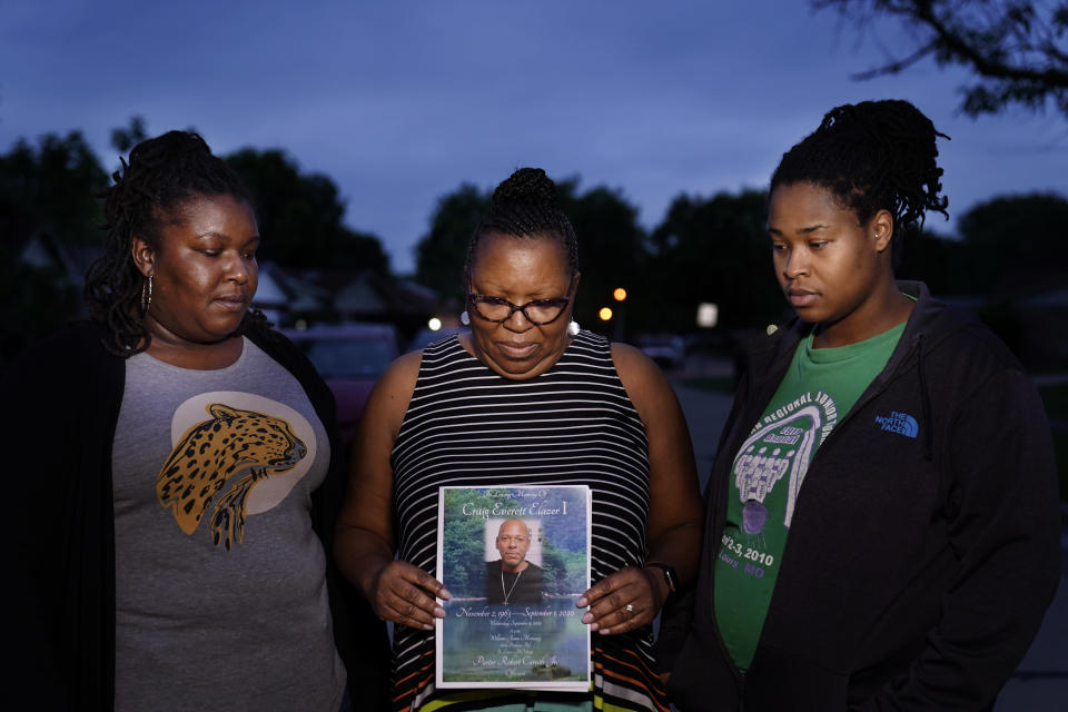 Michelle Branch, center, holds a pamphlet from the memorial service of her younger brother, Craig Elazer, 56, along with Elazer's stepdaughter, Shatia Jones, right, and niece, Alexa Sanders, in St. Louis on Monday, May 17, 2021. Elazer had struggled all his life with anxiety so bad his whole body would shake. But because he was Black, he was seen as unruly, not as a person who needed help, Branch says. He had started taking drugs to numb his nerves before he was old enough to drive a car. (AP Photo/Brynn Anderson)