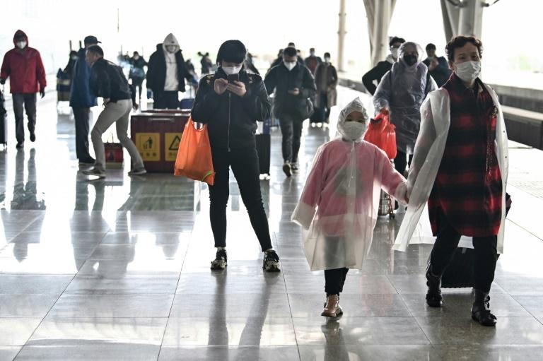 Passengers arrive at the railway station in Wuhan, China's central Hubei province, after travel restrictions into the city were eased following two months of lockdown