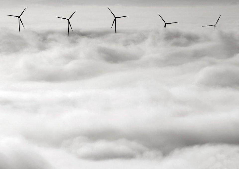 Wind turbines stand out from a dense blanket of fog covering Pamplona, northern Spain (EPA)