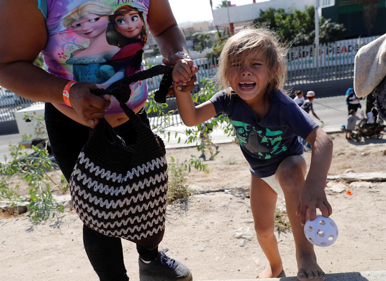 A migrant girl from Honduras, part of a caravan of thousands traveling from Central America en route to the United States, cries after running away from tear gas thrown by the U.S. border control near the border wall between the U.S. and Mexico in Tijuana, Mexico November 25, 2018. (Kim Kyung-Hoon/Reuters)
