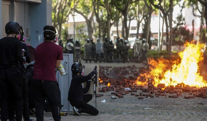 Protesters throw petrol bombs at police during clashes outside Polytechnic University. Photo: Winson Wong