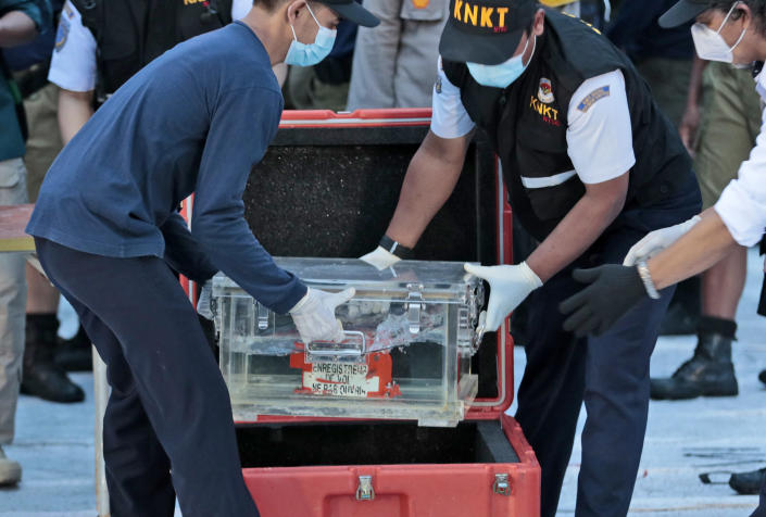 Members of National Transportation Safety Committee place a box containing the flight data recorder of Sriwijaya Air flight SJ-182 retrieved from the Java Sea where the passenger jet crashed into a container after a press conference at Tanjung Priok Port, Tuesday, Jan. 12, 2021. Indonesian navy divers searching the ocean floor on Tuesday recovered the flight data recorder from a Sriwijaya Air jet that crashed into the Java Sea with 62 people on board. (AP Photo/Dita Alangkara)