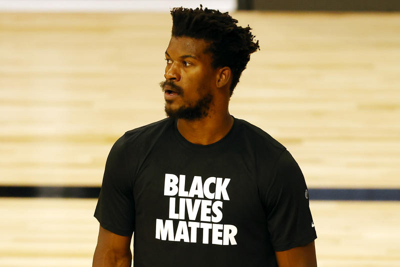 Jimmy Butler wears a Black Lives Matter t-shirt on a basketball court.
