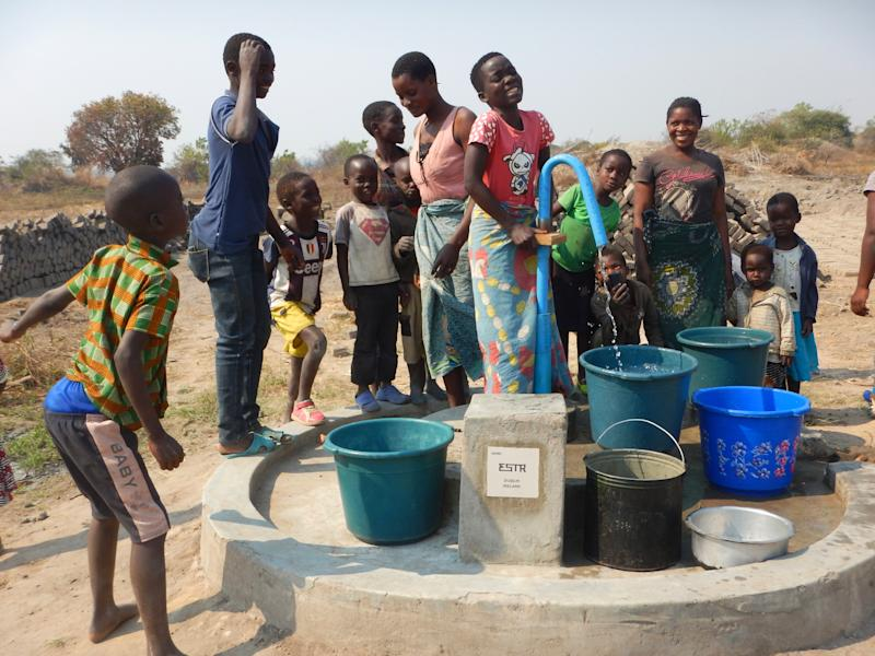 Members of a community in Northern Malawi gather around a water pump installed with assistance from the Wells for Zoë charity. (Wells for Zoë/Flickr)