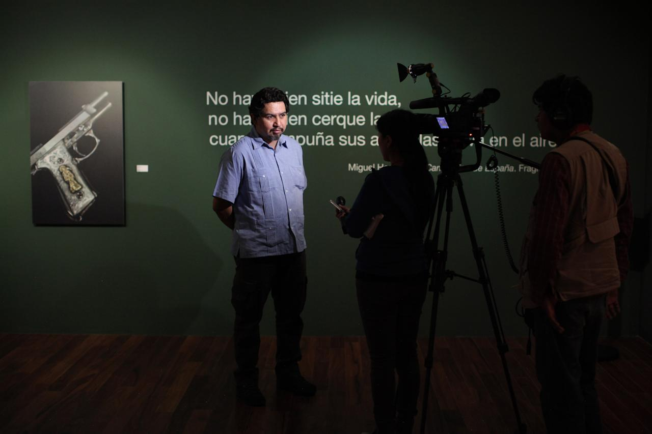 """In this Monday April 2, 2012 photo, photographer Gustavo Hoyos is interviewed at the art exhibit """"Goodbye to weapons. Smuggling on the border,"""" at which some of his work is on display at the Memory and Tolerance Museum in Mexico City. The exhibit highlights the impact of arms trafficking from the U.S. to Latin America, and will travel to Congress in Washington D.C. in August. (AP Photo/Alexandre Meneghini)"""