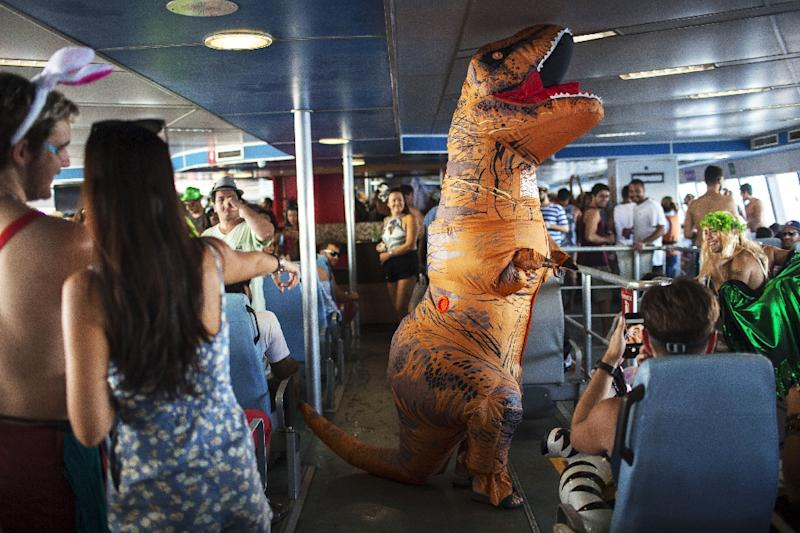 """A reveler performs on a ferry boat to Paqueta Island, on the way to the """"Perola da Guanabara"""" (Guanabara Pearl) street carnival, one of more than 100 parties planned a week ahead of Rio dethe sumptuous Sambodromo stadium carnival parades (AFP Photo/MAURO PIMENTEL)"""