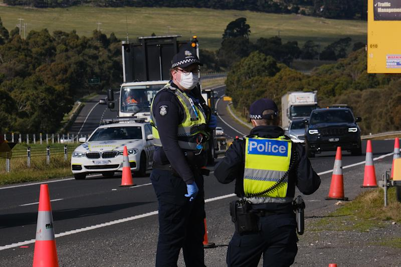 Pictured a Victoria Police officers enforcing lockdown measures on a highway.
