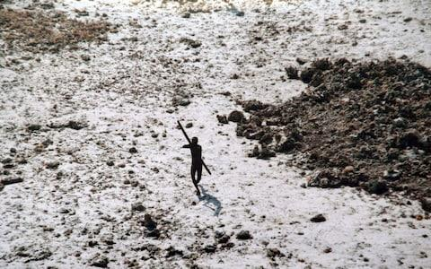 A Sentinelese man takes aim with a bow and arrow at an Indian Coast Guard helicopter in the wake of the 2004 tsunami - Credit: HANDOUT/AFP