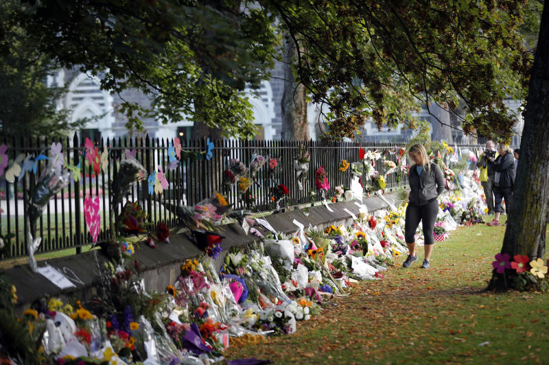 Mourners paying their respects at a makeshift memorial at the Botanical Gardens in Christchurch, New Zealand, Saturday, March 16, 2019. New Zealand's stricken residents reached out to Muslims in their neighborhoods and around the country on Saturday, in a fierce determination to show kindness to a community in pain as a 28-year-old white supremacist stood silently before a judge, accused in mass shootings at two mosques that left dozens of people dead. (AP Photo/Vincent Thian)