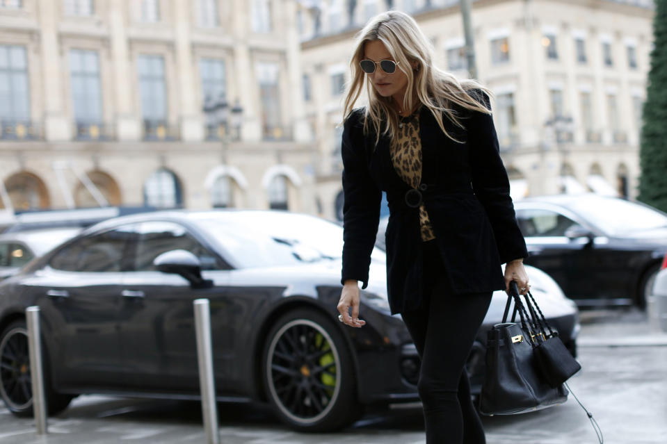 Kate Moss walks past a luxury car as she arrives at Paris Fashion Week earlier this year. Photo: Getty