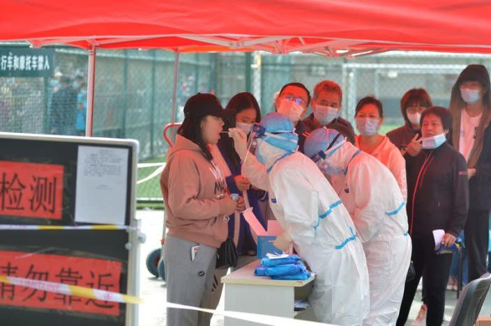 Medical workers in protective suits collect swabs for nucleic acid tests in Qingdao
