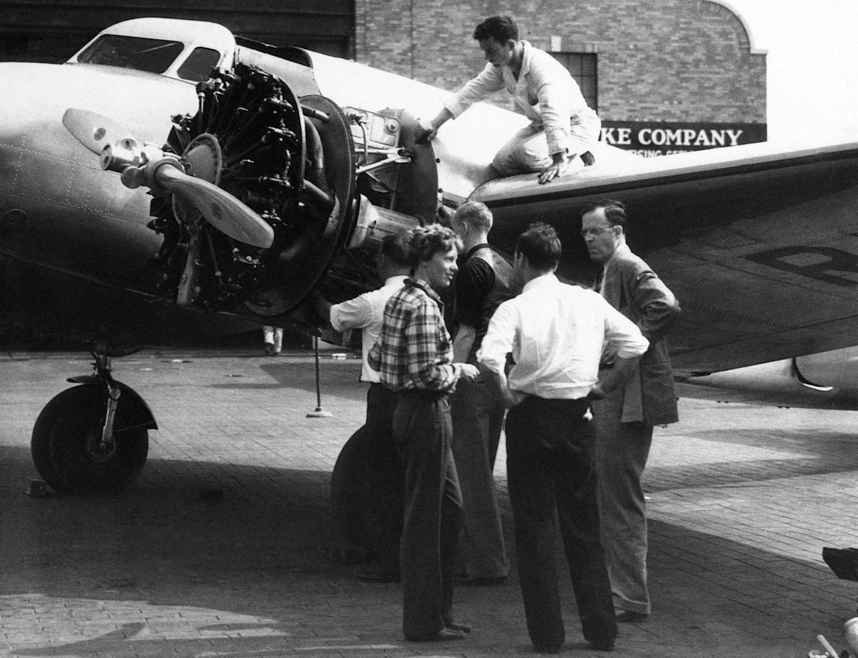 FILE - In this Sept. 4, 1936 file photo, Amelia Earhart is talking with her husband George Palmer Putnam, right, and friends in New York, before taking off from Brooklyn's Floyd Bennett field for Los Angeles in the Bendix Trophy race. Floyd Bennett Field was built between 1928 and 1931 and quickly became the preferred launching site for record-setting flights by Howard Hughes, Earhart, Wiley Post and other aviation pioneers. The Navy took over the airport in 1941 and most of the airport closed for good in 1971, but the New York Police Department still uses a corner of it as its helicopter base. (AP Photo, File)