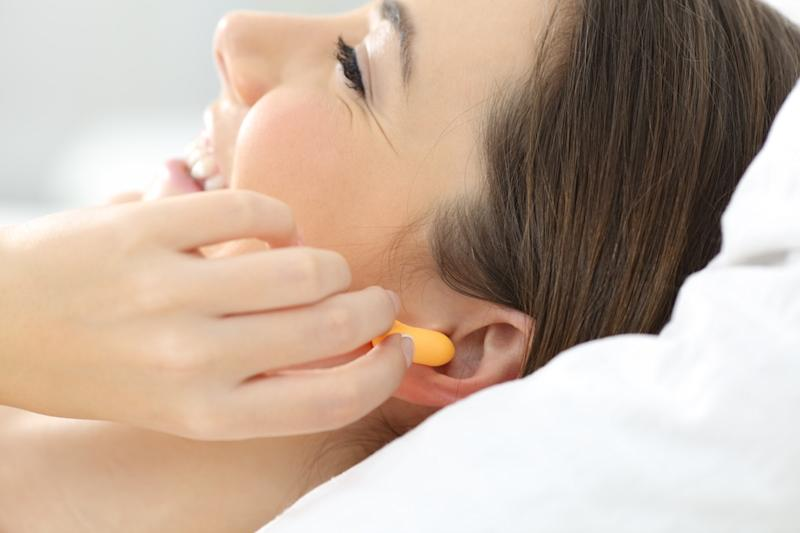 woman hand putting ear plugs to sleep on a bed at home
