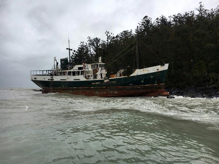 A vessel sits on the rocks after running aground near the Whitsunday Islands during Cyclone Debbie