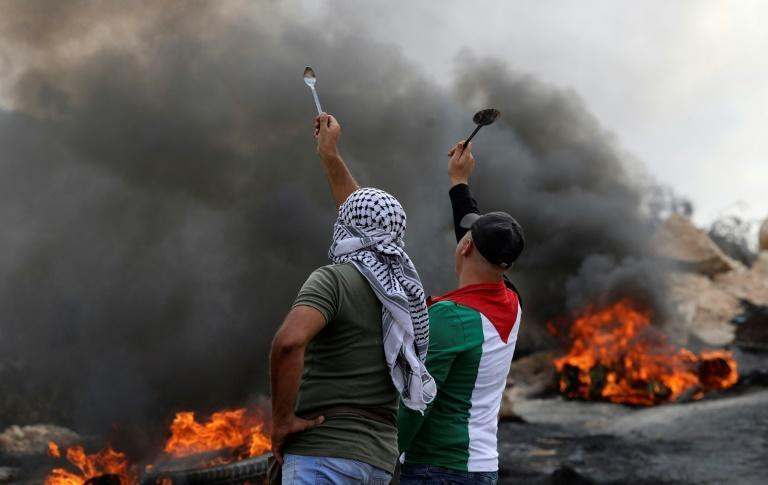 Palestinian protesters hold up spoons as they confront Israeli security forces in the West Bank village of Beita, on September 10, 2021 (AFP/JAAFAR ASHTIYEH)