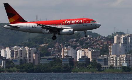 FILE PHOTO: An Airbus A318 airplane of Avianca Brazil flies over the Guanabara Bay as it prepares to land at Santos Dumont airport in Rio de Janeiro