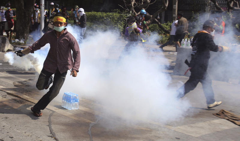 An anti-government protester runs with tear gas canister fired by riot police in Bangkok, Monday, Dec. 2, 2013. Thailand's Prime Minister Yingluck Shinawatra on Monday rejected the demands of anti-government protesters locked in street battles with police, saying what they want is unacceptable under the constitution.(AP Photo/Sakchai Lalit)