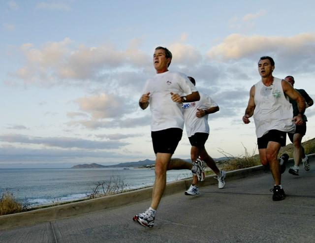 In 2002, then-President George W. Bush jogs with U.S. Secret Service agents during the APEC Leaders' annual meetings in Los Cabos, Mexico. (Photo: Larry Downing/Reuters)