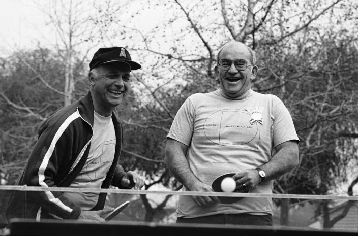 FILE - In this Jan. 6, 1980 file photo, from left, actor Gavin MacLeod and actor Ed Asner paddle away during a local art museum fund-raising ping-pong tournament in Downey, Calif. Gavin MacLeod has died. His nephew told the trade paper Variety that MacLeod died early Saturday, May 29, 2021. (AP Photo/George Brich, File)