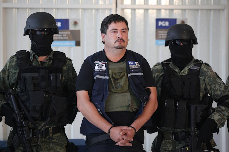 Army officers escort Ovidio Limon Sanchez, center, during his presentation to the media  in Mexico City, Thursday, Nov. 10, 2011. Limon Sanchez is an alleged top operator for the power Sinaloa drug cartel and one of the most-wanted U.S. drug fugitives in Mexico. (AP Photo/Alexandre Meneghini)