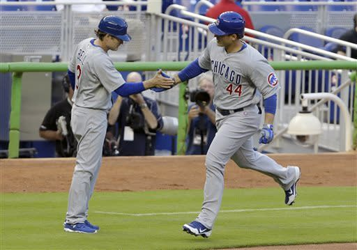 Chicago Cubs third base coach David Bell, left, congratulates Anthony Rizzo who heads for home after hitting a two-run home run during the first inning of a baseball game against the Miami Marlins, Friday, April 26, 2013, in Miami. Dave Sappelt also scored on the play. (AP Photo/Wilfredo Lee)