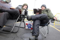 Rabbi Daniel Wasserman of Shaare Torah Congregation in Pittsburgh,, left, studies the Talmud with another man while tailgating in the parking lot of MetLife Stadium, Wednesday, Jan. 1, 2020, in East Rutherford, N.J., at an event called Siyum HaShas, that celebrates the completion of the reading of the Babylonian Talmud, a process that takes 7 1/2 years The large gathering of Jews drew a significant security presence after recent anti-Semitic attacks in the New York City area. (AP Photo/Ted Shaffrey)