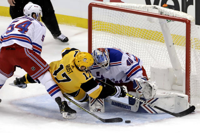 Pittsburgh Penguins' Bryan Rust (17) collides with New York Rangers goaltender Alexandar Georgiev (40) as Rangers' Adam McQuaid (54) defends during the first period of an NHL hockey game in Pittsburgh, Sunday, Feb. 17, 2019. (AP Photo/Gene J. Puskar)