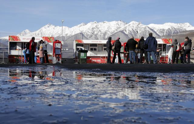 People stand near food stalls on a sunny day at the Sanki Sliding Center in Rosa Khutor, a venue for the Sochi 2014 Winter Olympics near Sochi, February 12, 2014. REUTERS/Fabrizio Bensch (RUSSIA - Tags: SPORT OLYMPICS FOOD ENVIRONMENT)