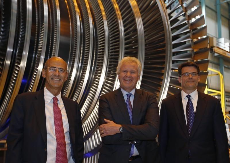 GE Chairman and CEO Immelt, Alstom Chairman and Chief Executive Kron and Bolze, president and CEO of GE Power & Water, pose for a picture in front off a steam turbine during a visit at the turbines production unit of the Alstom plant in Belfort