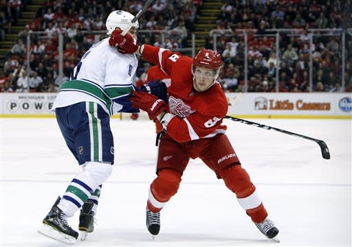 Detroit Red Wings left wing Justin Abdelkader (8) skates past Vancouver Canucks defenseman Sami Salo (6), of Finland, in the first period of an NHL hockey game in Detroit, Thursday, Feb. 23, 2012. (AP Photo/Paul Sancya)