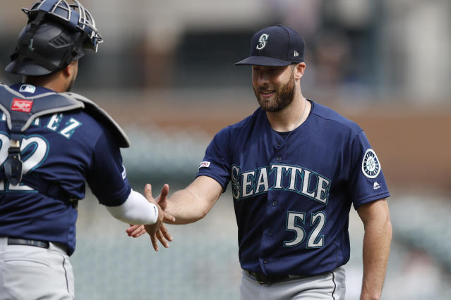 Seattle Mariners relief pitcher Anthony Bass (52) shakes hands with catcher Omar Narvaez after the Mariners' 7-2 win over the Detroit Tigers in a baseball game, Thursday, Aug. 15, 2019, in Detroit. (AP Photo/Carlos Osorio)