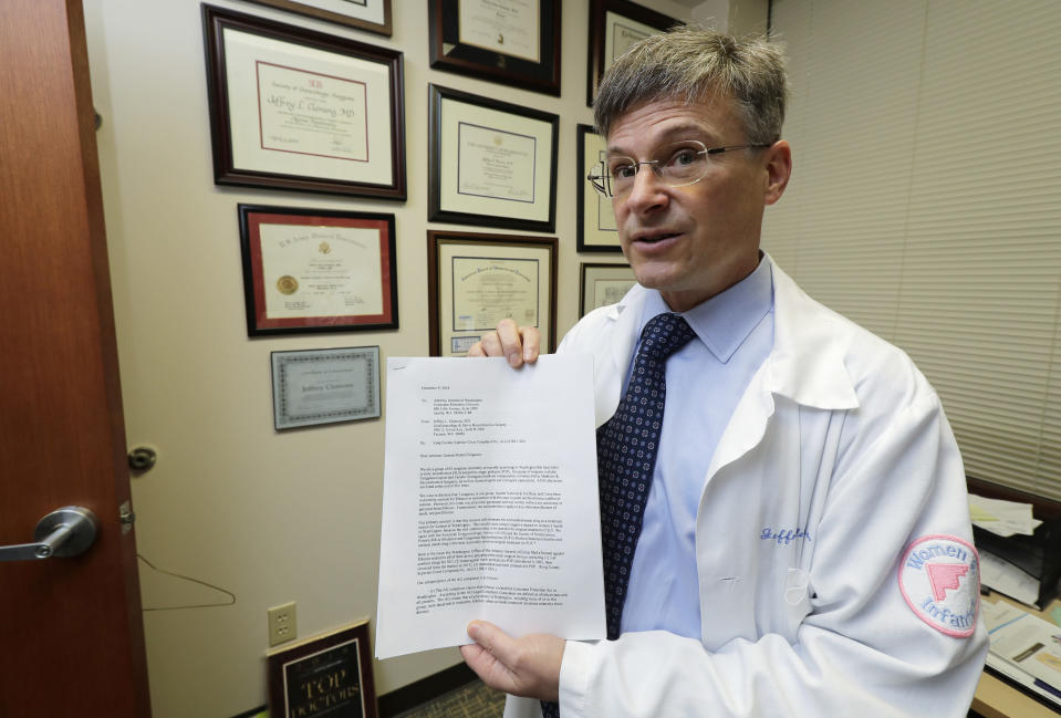 In this Dec. 20, 2018, photo, Dr. Jeffrey Clemons, a pelvic reconstructive surgeon, poses for a photo in Tacoma, Wash., with a letter to state Attorney General Bob Ferguson that he helped draft and was signed by more than 60 Washington state surgeons. The letter argues that Ferguson's consumer-protection lawsuit against Johnson & Johnson and its Ethicon Inc. subsidiary over products used to treat pelvic floor disorders and incontinence in women might scare patients away from the best treatment options. (AP Photo/Ted S. Warren)
