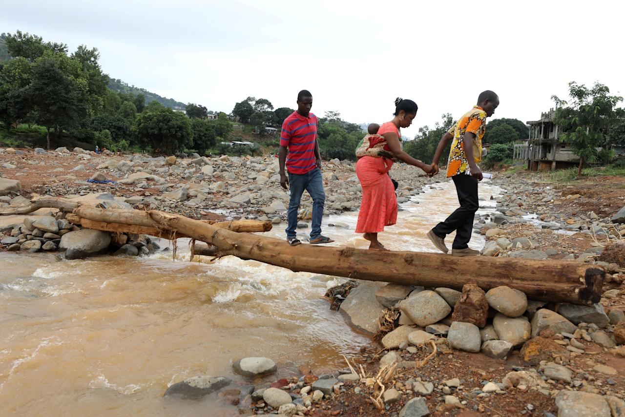 A man helps a woman cross a log bridge after the flash flood washed away a concrete bridge at Pentagon, in Freetown August 18, 2017. REUTERS/Afolabi Sotunde     TPX IMAGES OF THE DAY
