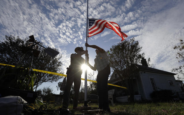 <p>A law enforcement officer helps a man changes a flag to half-staff near the scene of a shooting at the First Baptist Church of Sutherland Springs to honor victims, Monday, Nov. 6, 2017, in Sutherland Springs, Texas. (Photo: Eric Gay/AP) </p>