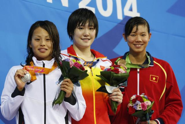Gold medallist Ye Shiwen of China (C) poses with silver medallist Sakiko Shimizu of Japan (L) and bronze medallist Thi Anh Vien Nguyen of Vietnam on the podium at the women's 400m individual medley final award ceremony at the Munhak Park Tae-hwan Aquatics Center during the 17th Asian Games in Incheon September 23, 2014. REUTERS/Tim Wimborne (SOUTH KOREA - Tags: SPORT SWIMMING)
