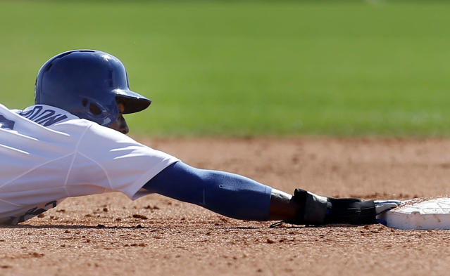 Los Angeles Dodgers' Dee Gordon holds on after sliding past second base on a steal against the Texas Rangers during a spring exhibition baseball game in Glendale, Ariz., Friday, March 7, 2014. (AP Photo/Paul Sancya)