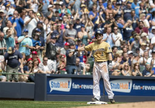 Milwaukee Brewers' Scooter Gennett waves after hitting a two RBI triple during the second inning of a baseball game, Sunday, June 9, 2013, in Milwaukee. (AP Photo/Tom Lynn)