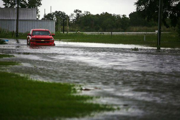 PHOTO: A car near Vermilion Bay drives through waters brought by Hurricane Laura approaching Abbeville, La., on Aug. 26, 2020. (Kathleen Flynn/Reuters)