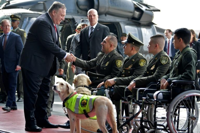 US Secretary of State Mike Pompeo (L) shakes hands with Colombian policemen victims of landmines during his visit at an anti-drug base in Bogota