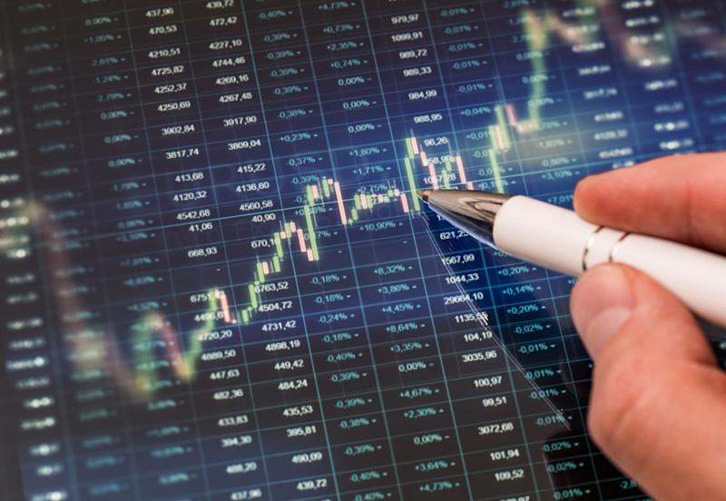 A hand holding a pen tracing a candlestick chart with stock tickers in the background.