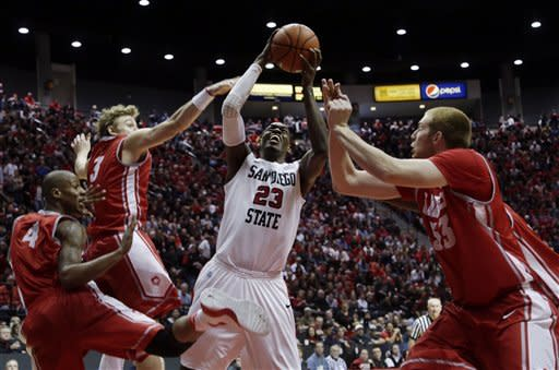 San Diego State's Deshawn Stephens, center, grabs an offensive rebound surrounded by New Mexico's Chad Adams (4), Hugh Greenwood (3) and Alex Kirk, right, in the second half during an NCAA college basketball game Saturday, Jan. 26, 2013, in San Diego. San Diego State won, 55-34. (AP Photo/Gregory Bull)