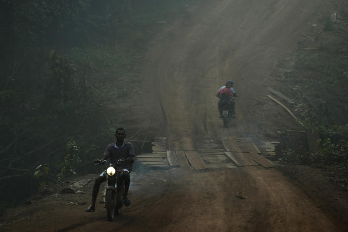 Residents motorcycle amid smoke from forest fires at dawn in the Vila Nova Samuel region, along the road to the National Forest of Jacunda, near the city of Porto Velho, Rondonia state, part of Brazil's Amazon, Aug. 25, 2019. (Photo: Eraldo Peres/AP)