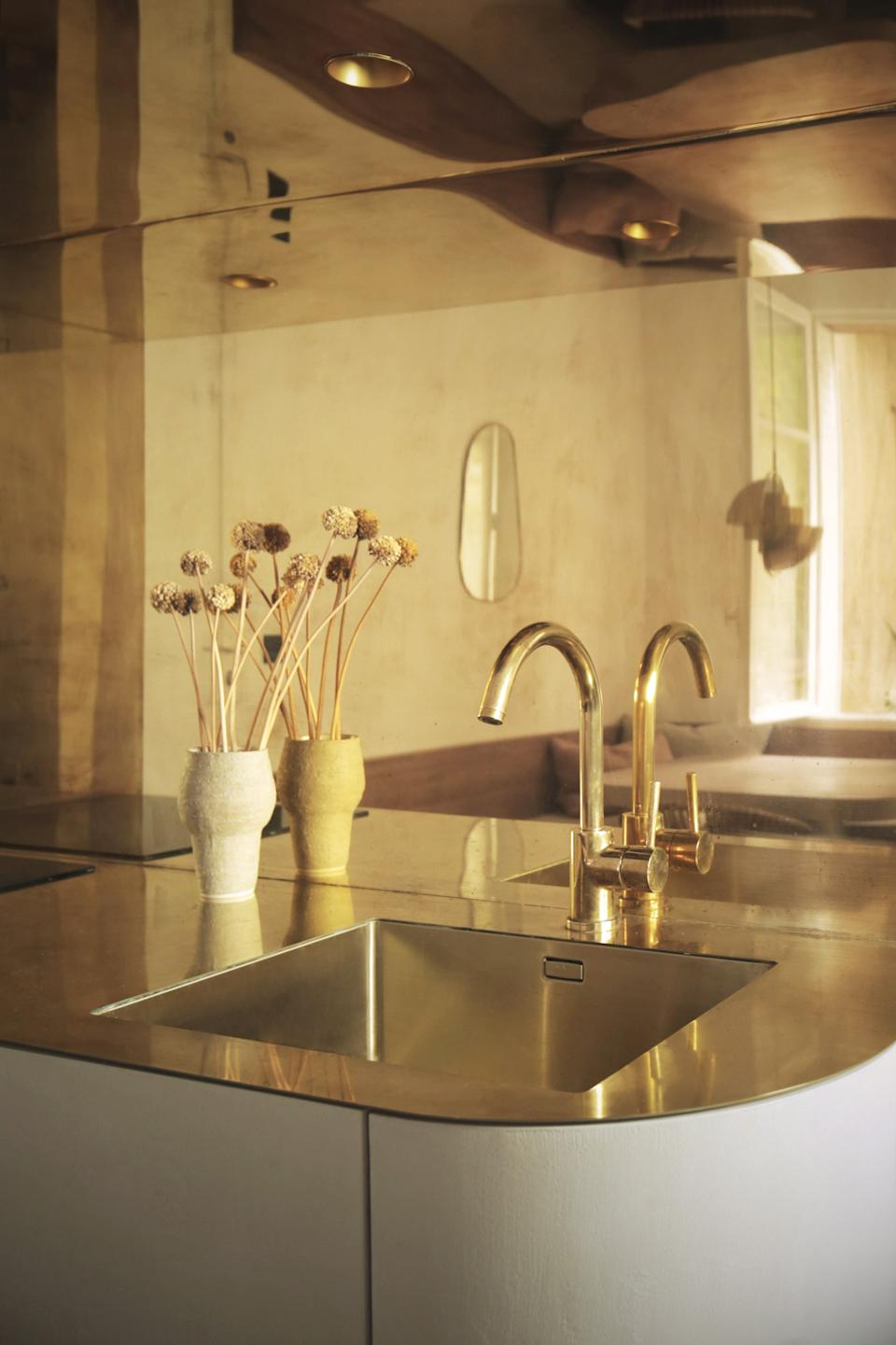 """<div class=""""caption""""> The shiny surface is accessorized with a contrasting matte vase and decor. </div>"""