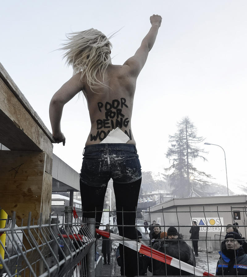An activist of the Ukrainian feminist  group FEMEN stands on a fence during a protest at the 43rd Annual Meeting of the World Economic Forum, WEF, in Davos, Switzerland, Saturday, Jan. 26, 2013.  (AP Photo/Keystone/Jean-Christophe Bott)